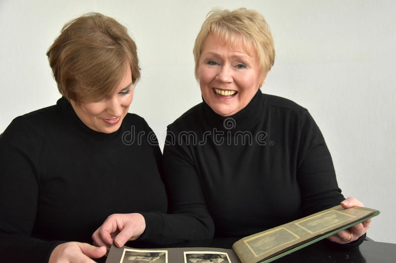 Mother and daughter looking at photo album. Mother and daughter having fun while looking at old pictures in a photo album stock photos