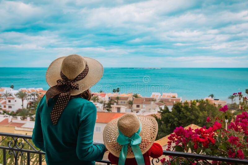 Mother and daughter looking at scenic view from the balcony stock photography