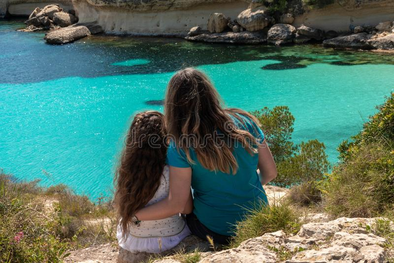 Mother and daughter looking at the sea stock images