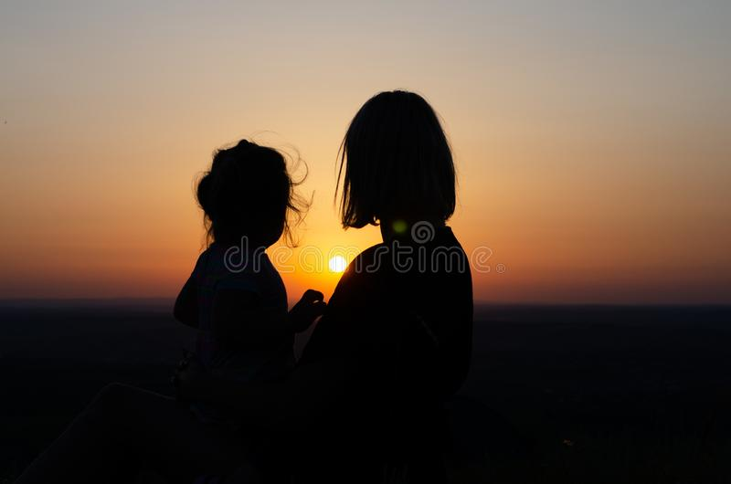 Mother and daughter looking  at the sunset stock images