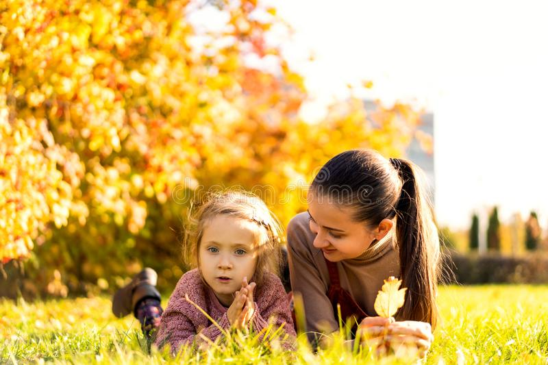 Mother with daughter in love walking in autumn park stock images