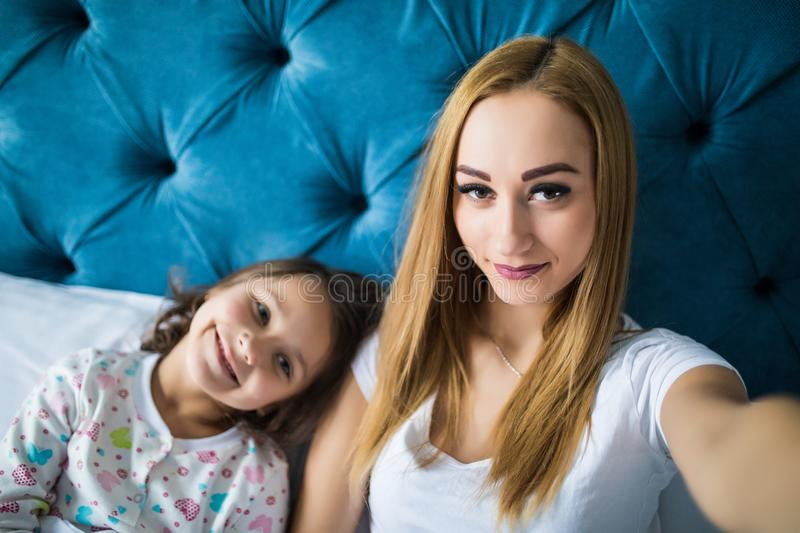 Mother and daughter lying on bed and taking self portrait with smartphone. Woman taking selfie on phone with a little girl in bedr royalty free stock photography