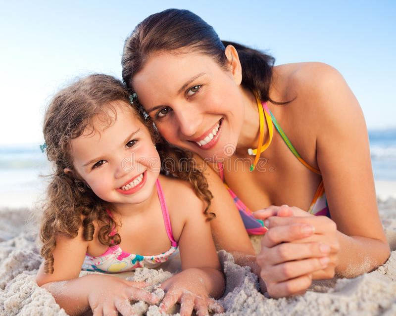 Mother and daughter lying down on the beach royalty free stock photography