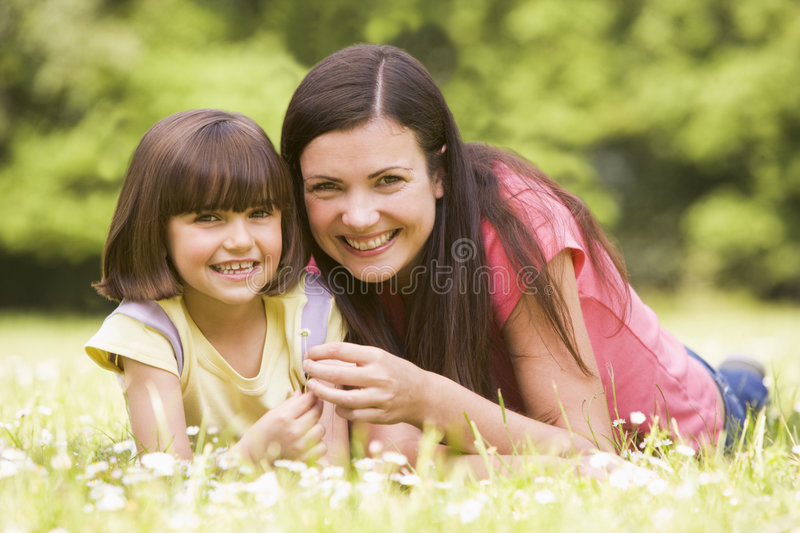 Mother and daughter lying outdoors with flower stock photo