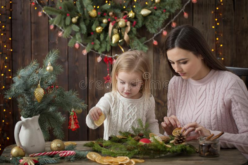 Mother and daughter make  Christmas wreath royalty free stock photo