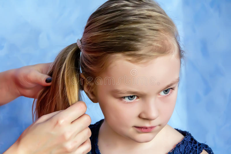 Mother and daughter makes hairstyle. Mother makes hairstyle to daughter on blue stock photos