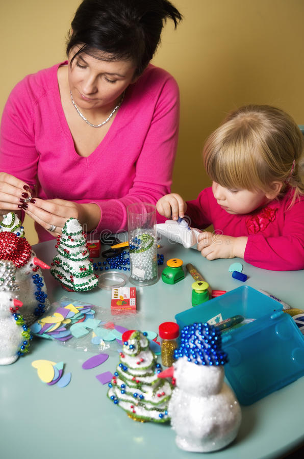 Mother and daughter making Christmas decorations