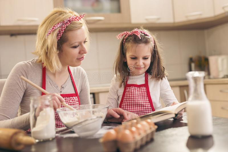 Mother and daughter reading instructions from a cookbook stock image