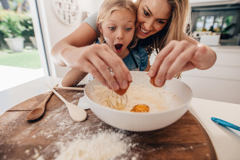 Mother and daughter making dough in kitchen stock image