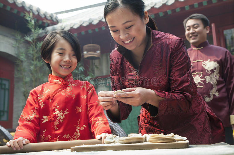 Mother and daughter making dumplings in traditional clothing royalty free stock images