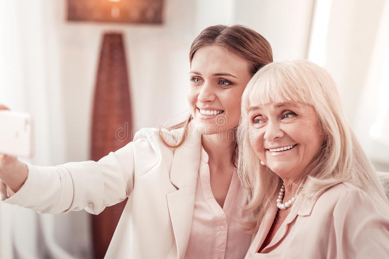 Mother and daughter making photos on a smartphone royalty free stock photos