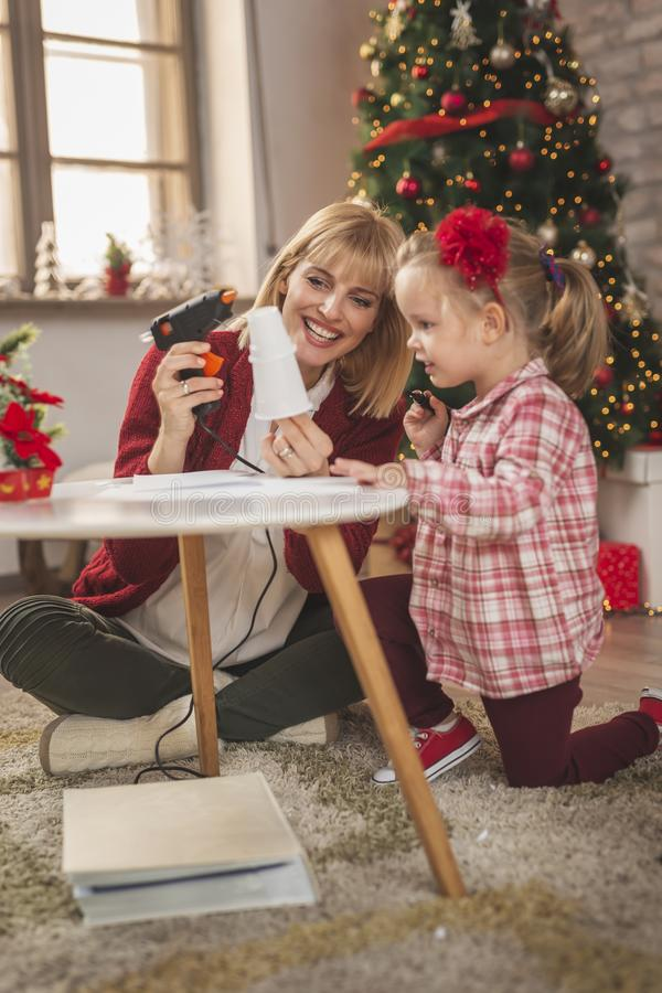 Mother and daughter making a snowman out of plastic cups stock photo