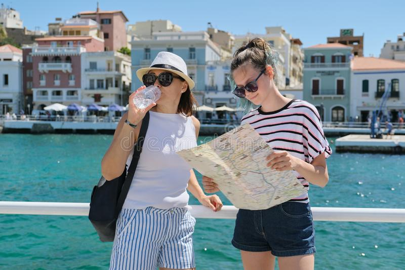 Mother and daughter with map on sunny day near sea promenade. Parent and teenager together, summer vacation in Mediterranean stock photos