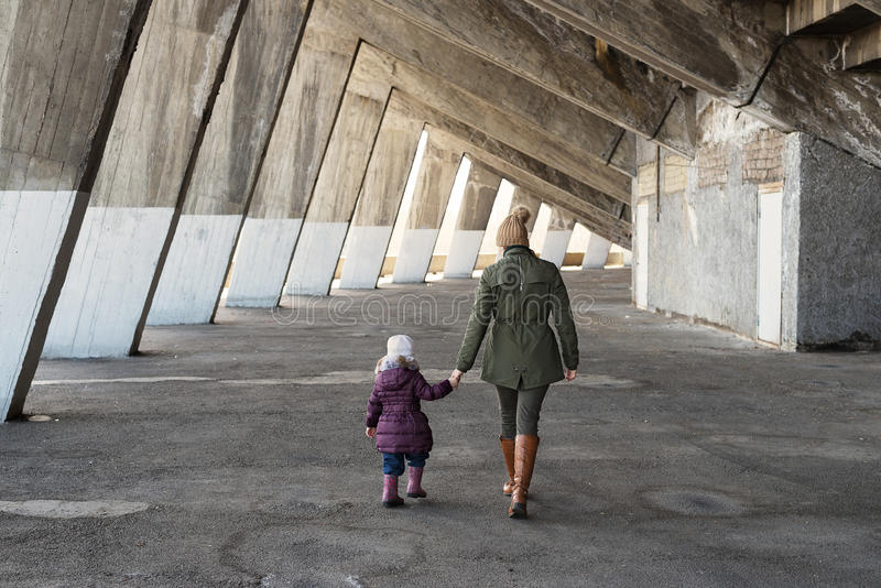 Mother and daughter in a massive grunge constraction. Mother and daughter walking hand in hand in an old massive grunge constraction royalty free stock photo