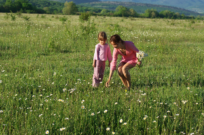 Mother and daughter on meadow stock images