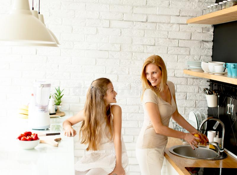Mother and daughter in the modern kitchen prepating food. Mother and daughter in the modern kitchen preparing healthy food stock photo