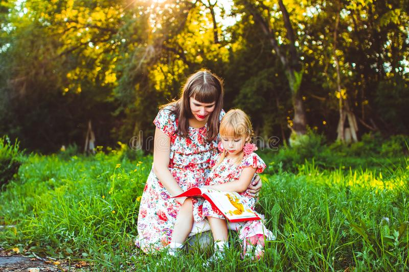 Mother and daughter on nature book stock images