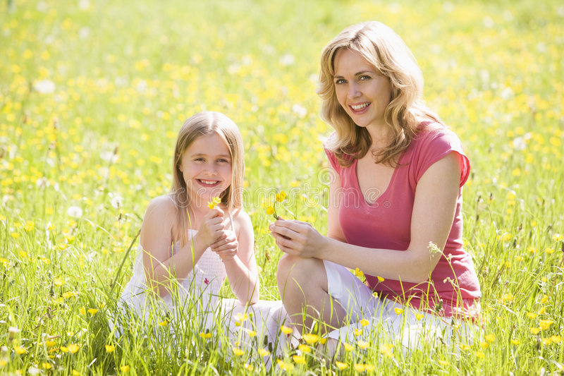 Download Mother And Daughter Outdoors Holding Flower Stock Photo - Image: 5935910