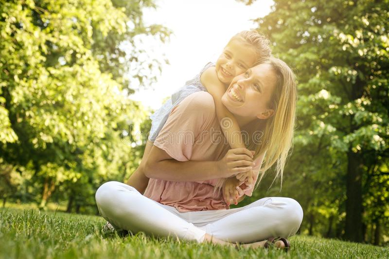 Mother and daughter outdoors in a meadow. Mother carrying her da royalty free stock images