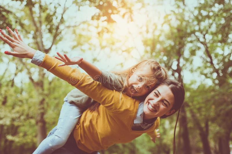 Mother and daughter outdoors in a meadow. Mother carrying her da stock photos