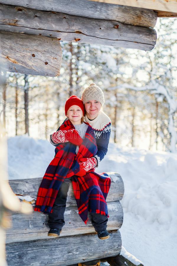Mother and daughter outdoors on winter. Beautiful family of mother and her little daughter enjoying snowy winter day outdoors royalty free stock photos