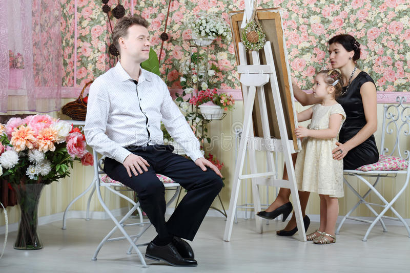 Mother and daughter paint portrait of man. Mother and daughter paint portrait of men in beautiful retro interior royalty free stock images