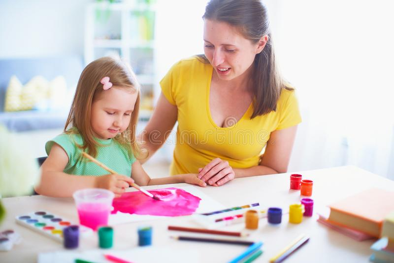 Mother daughter paints watercolor on a sheet of paper sitting at home at the table in a bright room royalty free stock photography