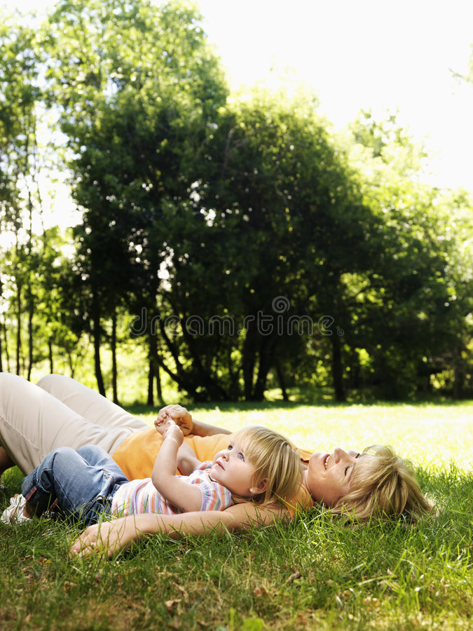 Mother and daughter in park. Caucasian mid adult woman with toddler daughter lying in grass at park relaxing stock photography