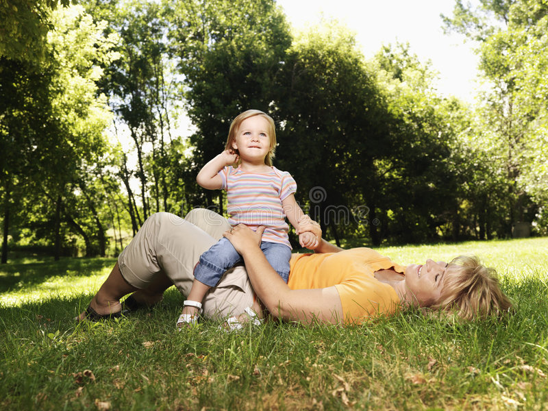 Mother and daughter in park. Caucasian mid adult woman lying in grass at park with toddler daughter seated on her lap stock images
