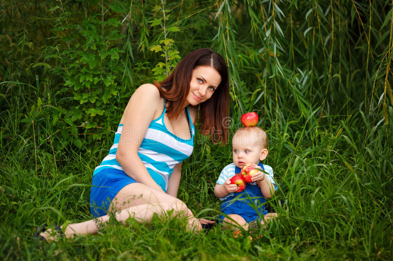 Mother and daughter in park. Daughter eating apples. royalty free stock photos