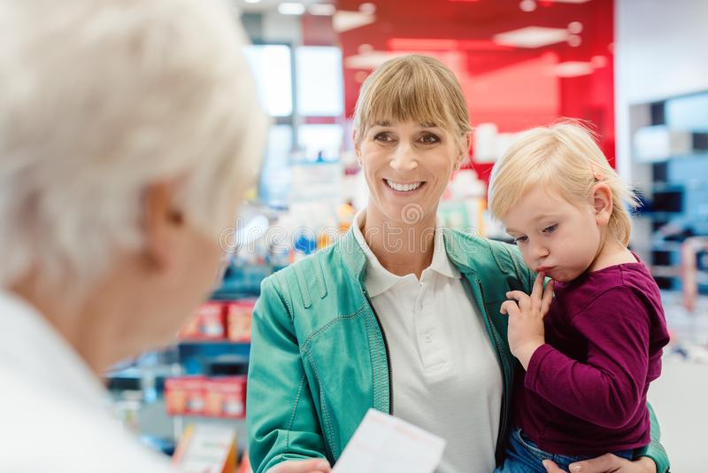 Mother with daughter in pharmacy at the counter stock photos