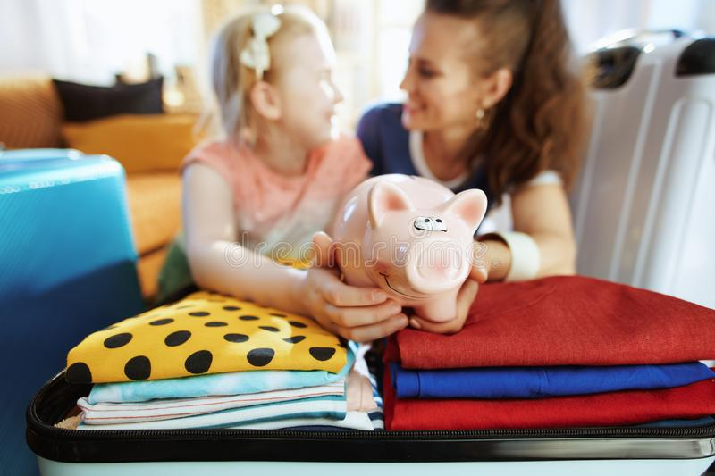Mother and daughter with piggy bank calculates travel budget. Happy young mother and daughter travellers with piggy bank calculates travel budget in the modern royalty free stock image