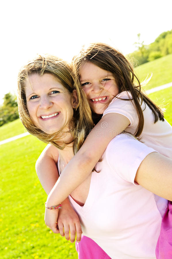 Mother and daughter piggyback stock images