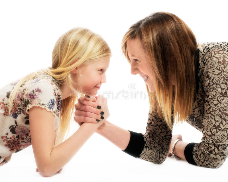 Mother & Daughter. Mother and daughter in playful arm wrestle royalty free stock image