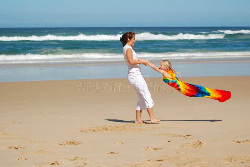 Mother and daughter playing. A beautiful young caucasian white mom playing and having fun with her little daughter while swinging her around on the beach in stock photos
