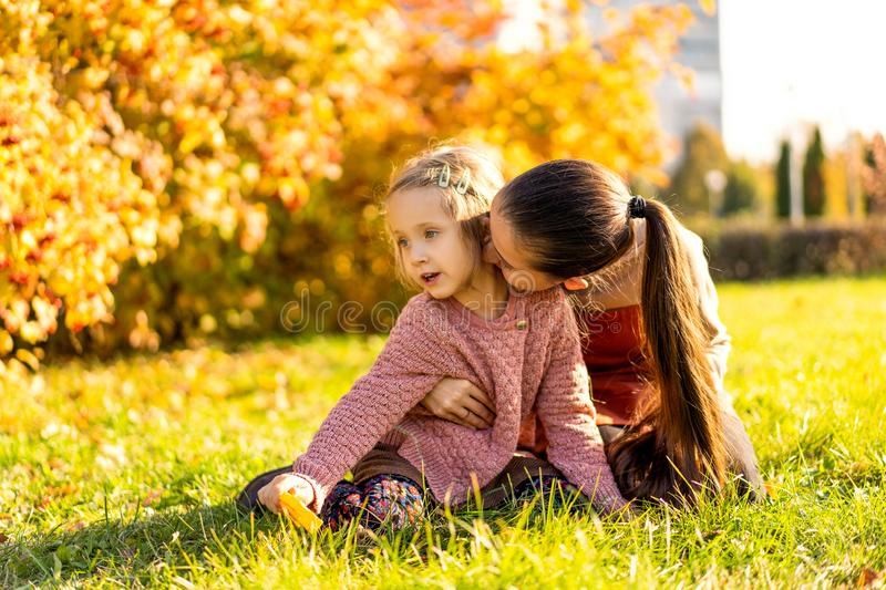 Mother and daughter playing in the autumn park royalty free stock photo