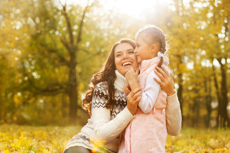 Mother and daughter playing in autumn park stock photos