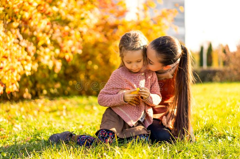 Mother and daughter playing in the autumn park royalty free stock image