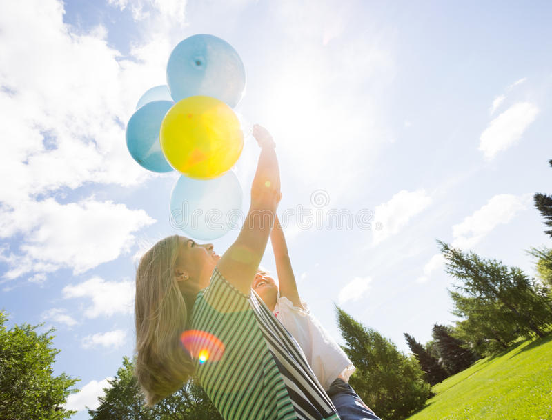 Mother And Daughter Playing With Balloons In Park stock image