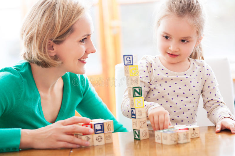 Mother and daughter playing with blocks stock photos