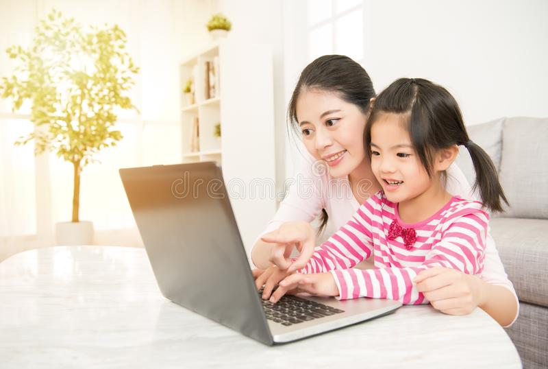 Mother and daughter playing computer stock photos