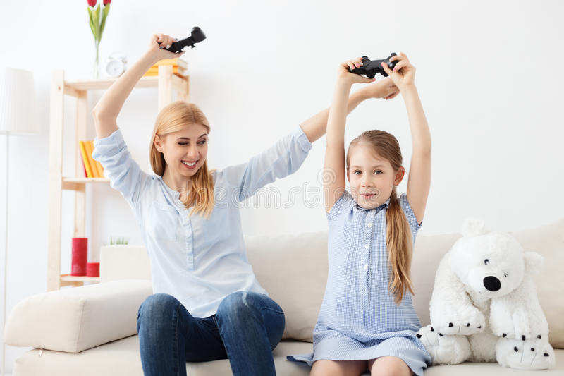 Mother and daughter playing on console stock photography