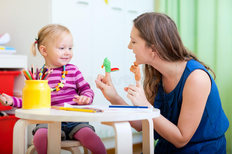 Mother and daughter playing with finger toys royalty free stock photography