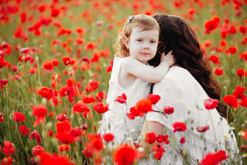 Mother and daughter playing in flower field stock photo