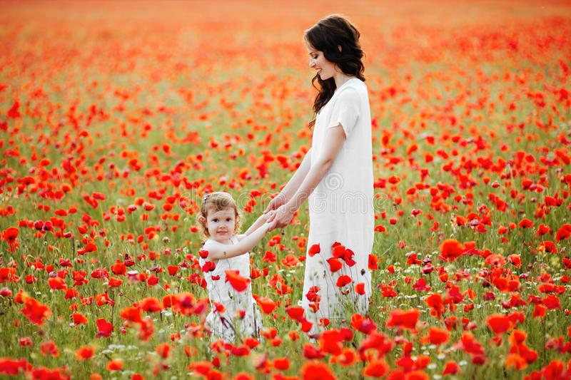 Mother and daughter playing in flower field royalty free stock photography