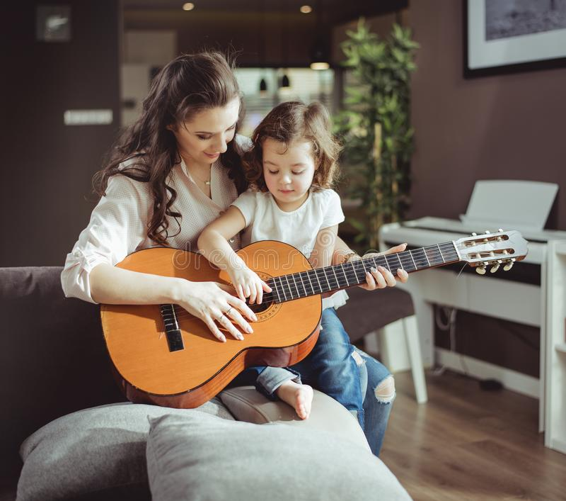 Young Happy Beautiful Family Playing Together On The Beach: Mother And Daughter Playing Guitar Stock Photo