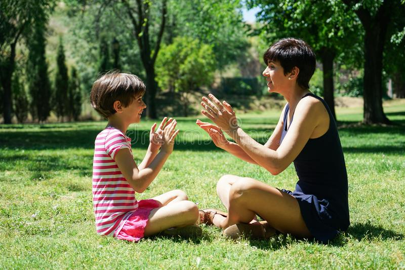 Mother and daughter playing with hands in city park royalty free stock image