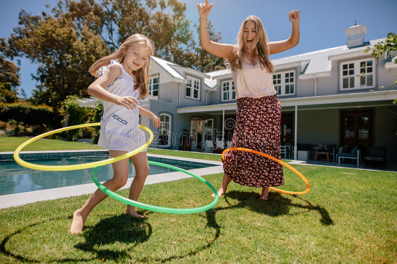 Mother and daughter playing with hula hoop in their backyard stock photography