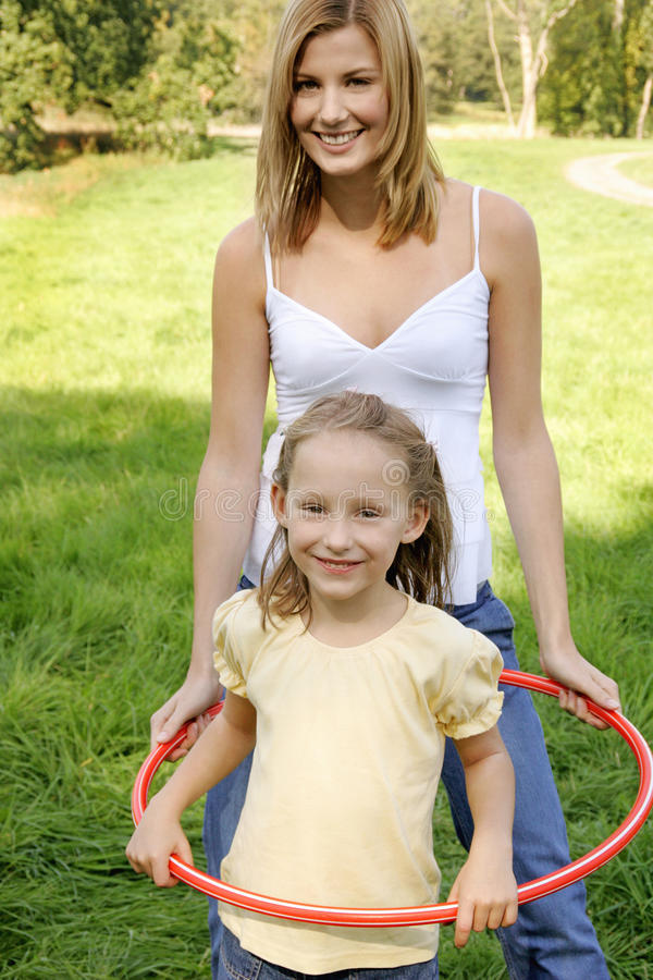 Mother and daughter playing with hula hoops. stock photo
