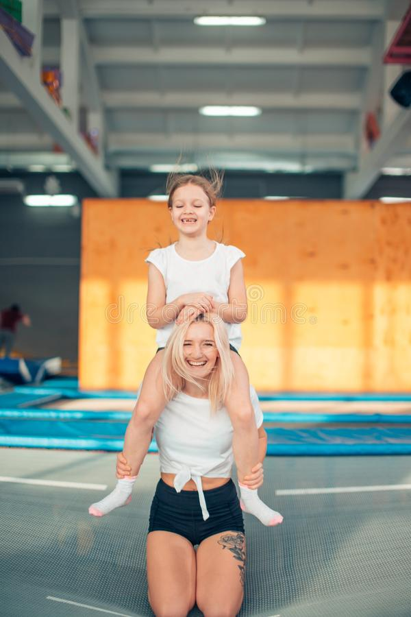 Mother and daughter playing at playground. girl sitting on her mother neck stock image